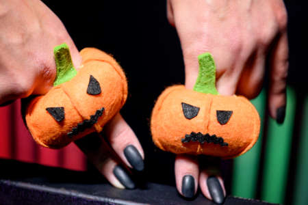 girls hands with a black manicure play in a puppet theater with toys in form of pumpkins for Halloween on the fingers