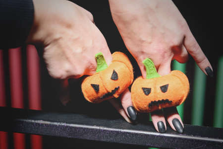 female hands with black manicure playing with puppets in form pumpkins for Halloween on fingers Zdjęcie Seryjne