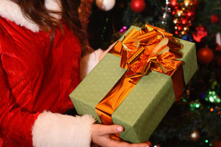 womans hands hold Christmas or new year gift box decorated with golden bow