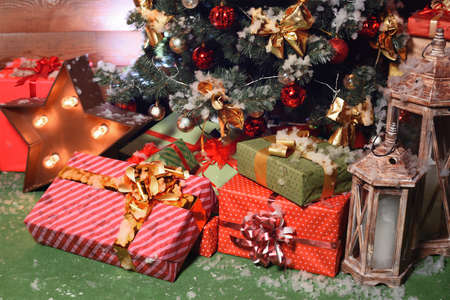 colorful Christmas gift boxes on floor near fir tree
