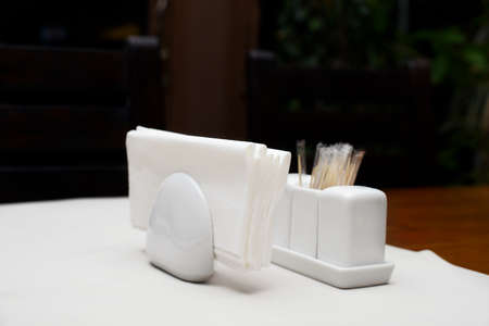 Paper napkins in the holder with salt pepper and toothpicks on table in restaurant Zdjęcie Seryjne