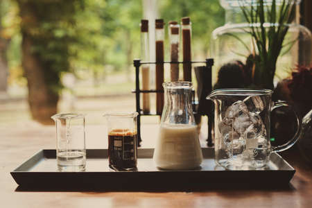 ingredients for making cold coffee latte, ice cubes espresso milk and sweet syrup served in various test tubes on wooden table in the morning cafe against of blurred window