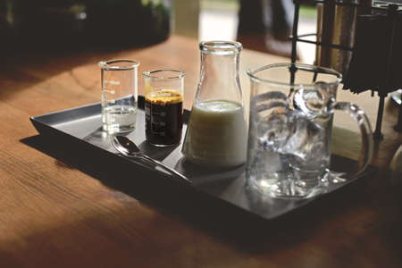 set for preparing iced coffee latte, ice cubes espresso milk and sweet syrup served in various test tubes on wooden table in morning cafe