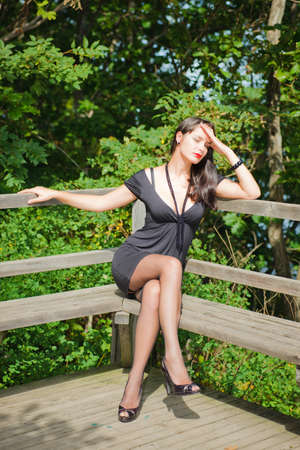 Fashion photography. Beautiful young sexy girl on a wooden bench in the park. Stock Photo - 8716430