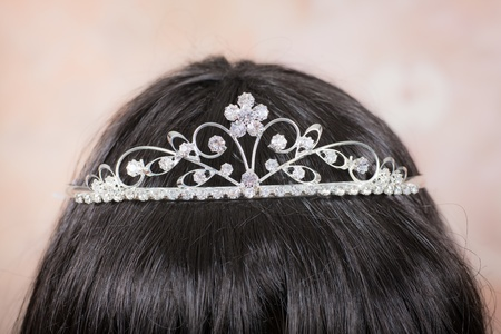 Beautiful tiara with artificial diamonds on the head of a girl with dark hair photo