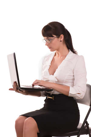beautiful business woman with dark hair wearing glasses is sitting with a laptop photo