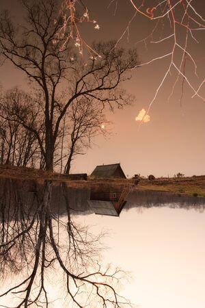 Paisaje de otoño. Cabaña destartalado en el árbol por el lago Foto de archivo - 8845056