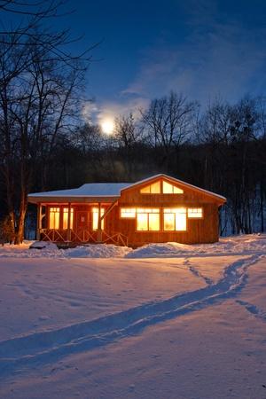cottage: en vacaciones de invierno madera chalet de madera con windows brillantes y chimeneas de fumar Foto de archivo
