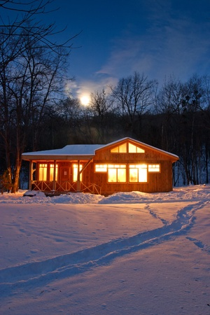 huts: in winter wood wooden chalet holiday with glowing windows and smoking chimneys Stock Photo