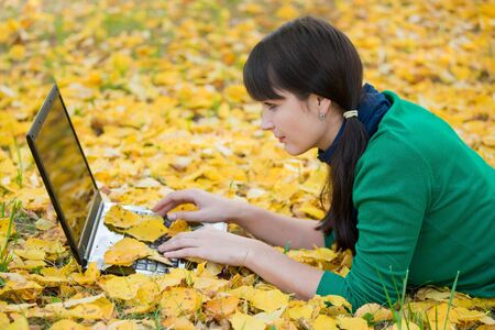 Autumn landscape. beautiful young girl resting in yellow autumn leaves Stock Photo