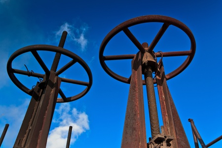 rusty pipes valves against the clear sky photo