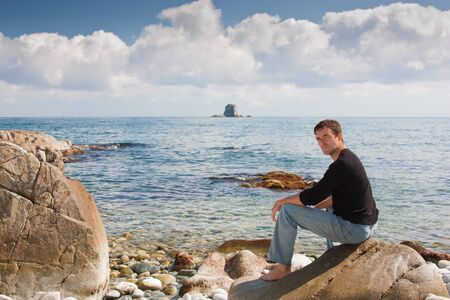handsome young man sitting on a rock on the beach photo
