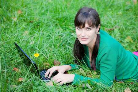 beautiful young girl who lies with a laptop on a green lawn photo