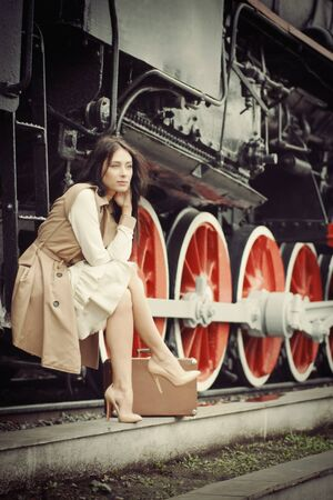 retro woman: girl waiting for landing on the platform in the vintage train
