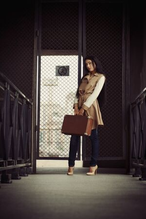brunette girl with brown suitcase stands at the gate photo