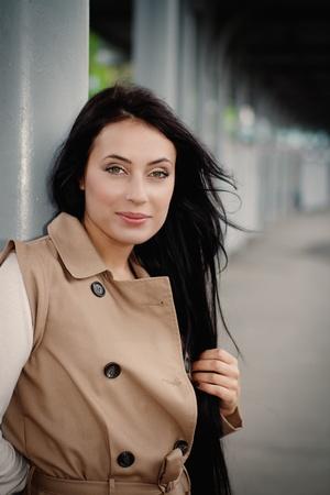 brunette girl waiting for train on platform photo
