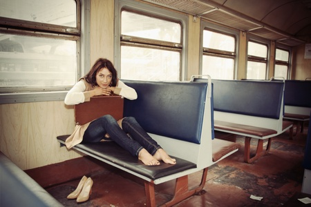 baggage train: brunette girl sitting  of a train Stock Photo