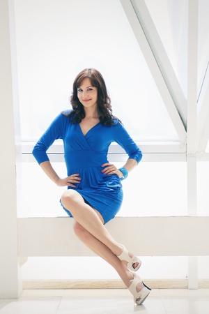 portrait fashion girl in a blue dress sitting on white box Stock Photo