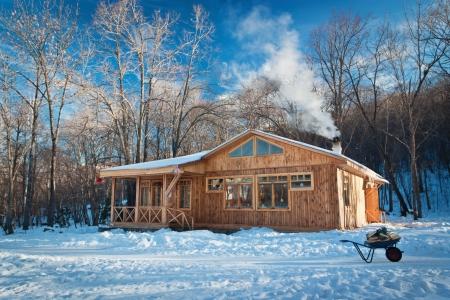 hospedaje: una pequeña casa de madera en un bosque cubierto de nieve