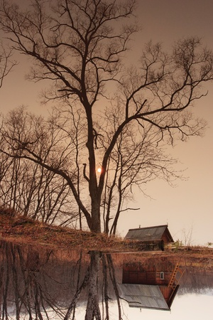 Autumn landscape. ramshackle hut in the tree by the lake Stock Photo - 12047851