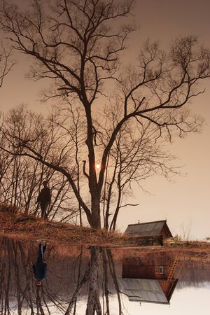 Autumn landscape. ramshackle hut in the tree by the lake Stock Photo - 12047859