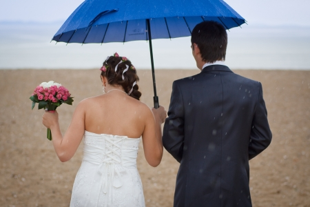 couple walking in the rain on the beach