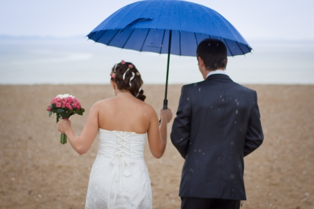 couple walking in the rain on the beach photo