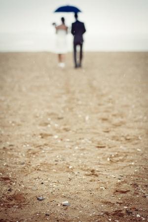 Pareja caminando en la lluvia en la playa Foto de archivo - 12034551