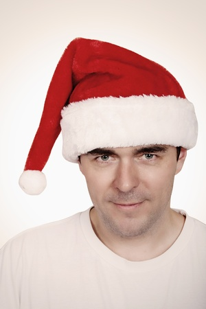 A young man with a beard in a red Christmas hat photo