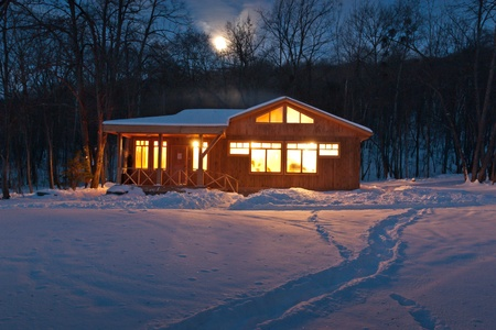 a small wooden house in a snowy forest Stock Photo