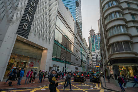 Hong Kong - 2020: Lan Fong Road, entrance to Lee Garden One. People stand in line at the bus stop, pedestrians cross the street. Editoriali