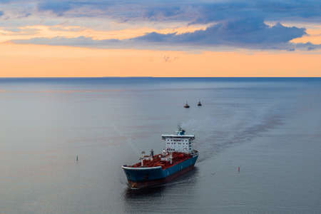 Tanker at sea, aerial view. Large blue and white ship in the bay at sunset. Landscape from above.