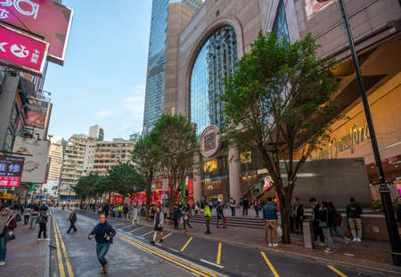 Hong Kong - 2020: Russell Street, Times Square mall entrance, people stand on the sidewalk and cross the road.