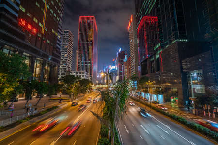 Hong Kong - 2020: Gloucester Road at night from above, street with palm trees and flower beds. Hong Kong Skyscrapers in night illumination. Cars in motion.