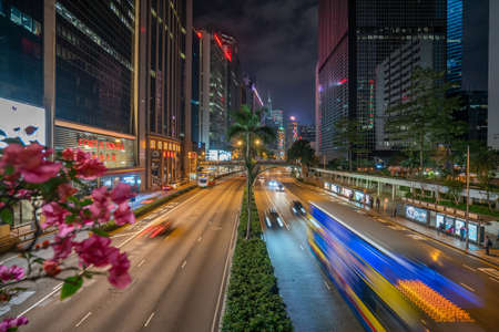 Hong Kong - 2020: Gloucester Road at night from above, a wide street with palm trees and flower beds. Fortis Tower, Gloucester Luk Kwok, Rhubarb Tower - skyscrapers in night illumination. Cars in motion. Editoriali