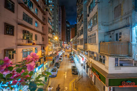 Hong Kong - 2020: residential area at night, view from the balcony with flowers, house, windows and balconies, the street is lit with lanterns, cars and motorbikes are parked at the side of the road.