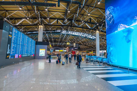 Moscow, Russia - 2020: interior of Sheremetyevo International Airport, Terminal C. Spacious hall, glazed ceiling, electronic displays, large video monitors. Passengers at the airport.