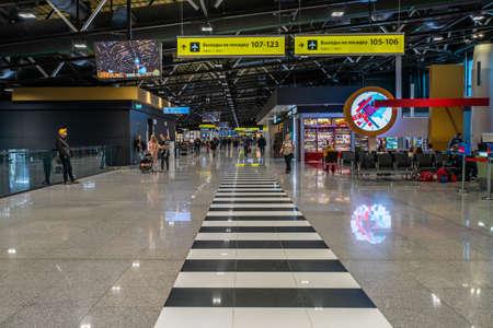 Moscow, Russia - 2020: Sheremetyevo International Airport interior, black and white crosswalk, passengers. Editoriali