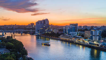 Rostov-on-Don, Russia - 2019: aerial view of the Don river, boat and promenade at sunset. Residential complex White Angel, bridges. Light of lanterns, beautiful sky with pink clouds.