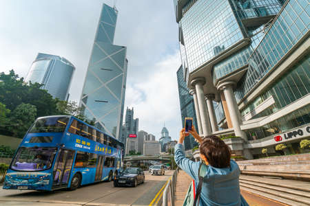 Hong Kong - 2020: woman taking pictures in the city, road with bus, skyscrapers - Lippo Centre and Bank of China Tower, beautiful cityscape.
