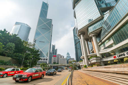 Hong Kong - 2020: Queensway, road with Hong Kong taxi, skyscrapers - Lippo Centre and Bank of China Tower, cityscape.