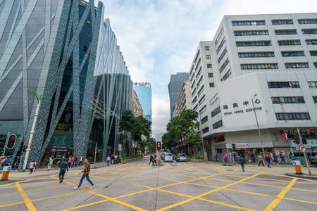 Hong Kong - 2020: crossroad, Centre Parc and Shui Hing Centre, people on the street, yellow road marking.