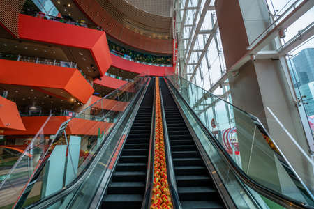 Hong Kong - 2020: escalator in MegaBox shopping center, without people, interior, empty escalator with glass railing.