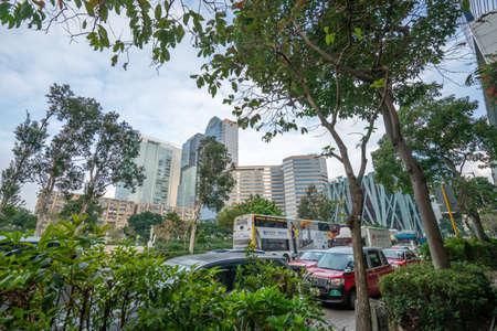 Hong Kong - 2020: Lum Fung Street, cars, buses, trees and office building - Enterprise Square, Centre Parc, Zero Carbon Park.
