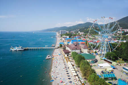 Lazarevskoe, Russia - 2016: Black sea, people on the beach, park and ferris wheel from above. Summer vacation. Editoriali