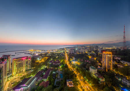 Sochi, Russia - 2016: city center at sunset from above, Mercure Hotel, houses roofs and treetops, Kurortny avenue, evening lights. Editoriali