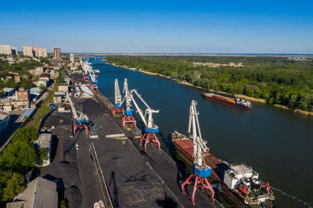 Rostov-on-Don, Russia - 2020: Don river, barges, port and cranes, coal loading, aerial view.