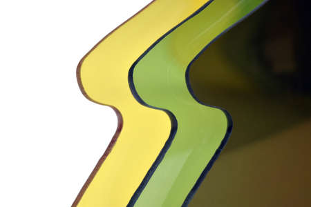 Abstract plastic background in yellow, green and brown colors. Close-up photo of plastic lenses for sunglasses