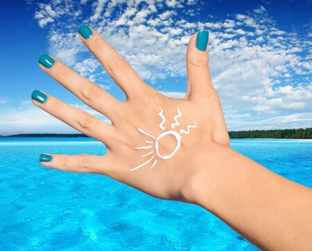 sunscreen lotion on woman hand photo