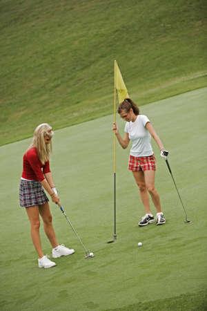 early 20s: Modelo de la etapa 35 en la mujer alrededor de los 20 a�os jugando golf  Foto de archivo
